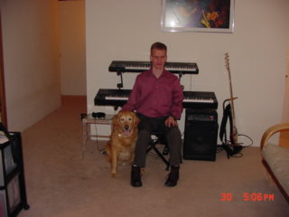 Photo of ivan and Seeing Eye dog Zeke, with two  keyboards and a bass in the background.